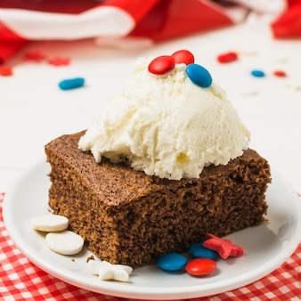 Delicious cake with ice cream scoop and candies on white plate for independence day