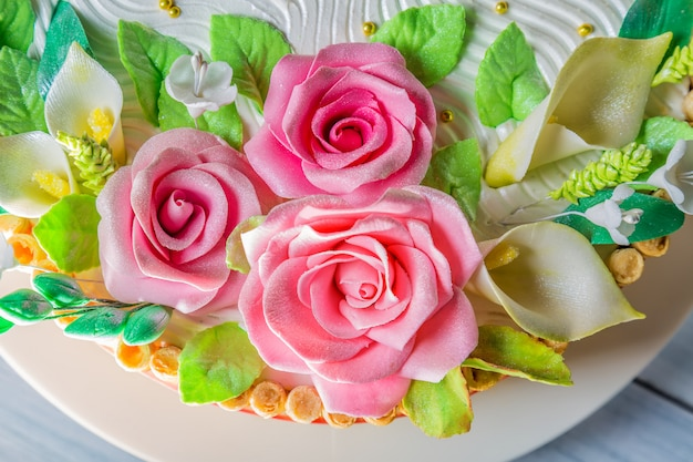 Delicious cake with roses, lily and leaves on light blue wooden table close up