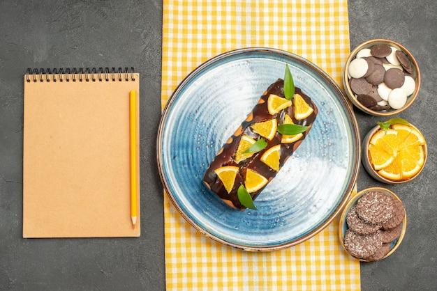 Deliziosa torta su asciugamano giallo e biscotti accanto al taccuino sulla tavola nera