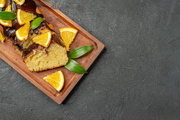 Delicious cakes decorated with orange and chocolate on wooden cutting board on black table