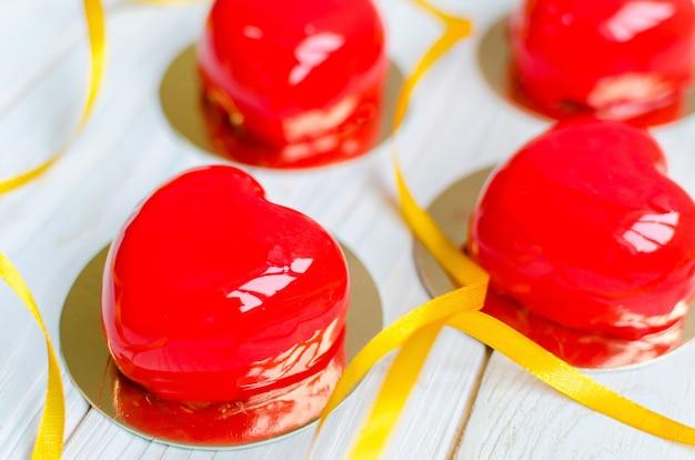 Вкусные пирожные в виде глянцевых красных сердечек.