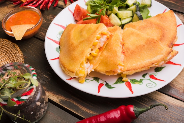 Delicious cakes near vegetable salad on plate among nachos with sauce and chili