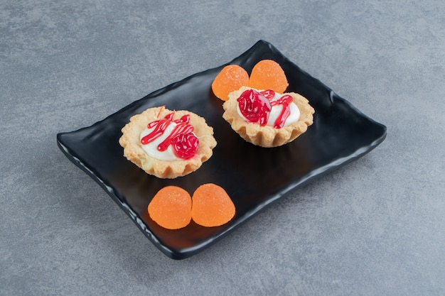 Delicious cakes with fruits and jelly candies