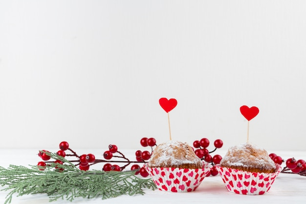 Delicious cakes with hearts on wands near twigs
