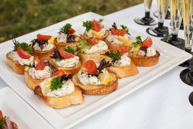 Delicious canape with sausage and tomato.canapes on white ceramic plates at wedding reception.