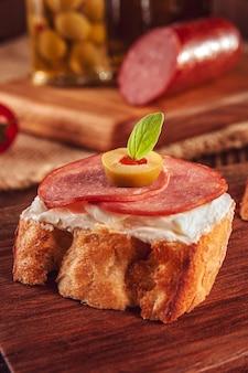サラミ、クリームチーズ、オリーブ、木製の背景にトマトのおいしいカナッペ