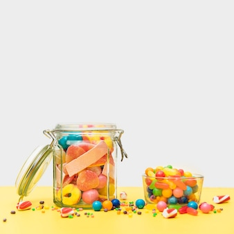 Delicious candies in jar and cup on table