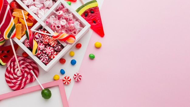 Delicious candies on pink table