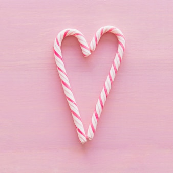 Delicious candy canes placed in form of heart
