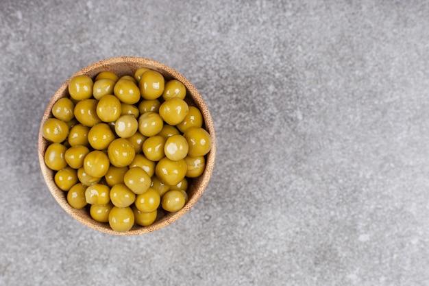 木製のボウルにおいしい缶詰のエンドウ豆