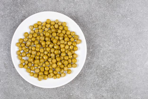 白いプレートにおいしい缶詰のエンドウ豆
