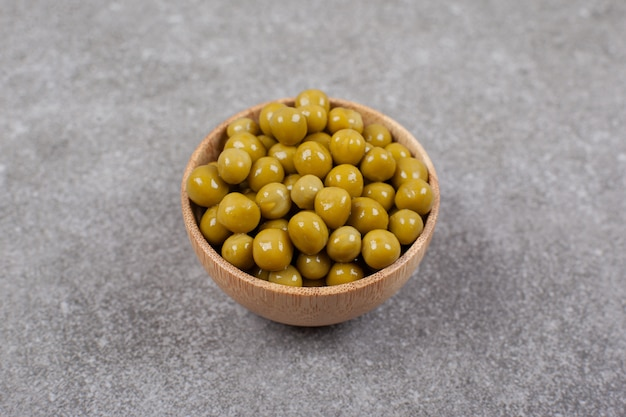 Delicious canned peas in wooden bowl