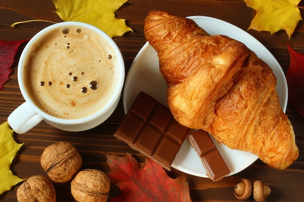 Delicious cappuccino, croissant and chocolate like autumn still life