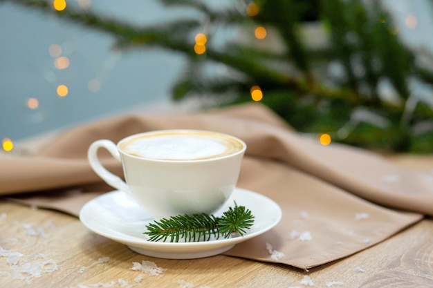 Delicious cappucino coffee cup, fireflies and spruce branches