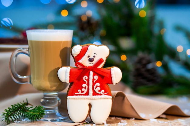 Delicious cappucino glass cup with christmas teddy bear gingerbread cookie.