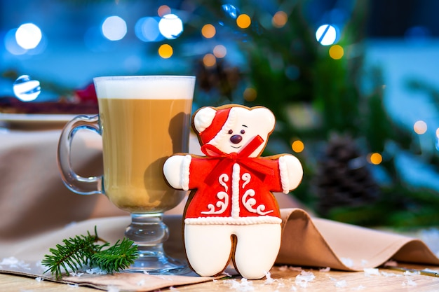 Delicious cappucino glass cup with christmas teddy bear gingerbread cookie