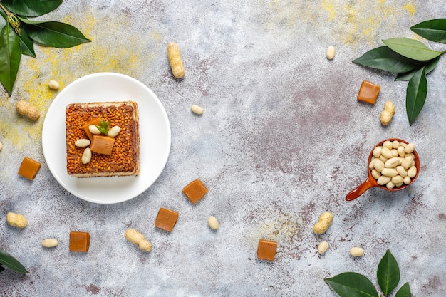 Delicious caramel and peanut cake with peanuts and caramel candies, top view