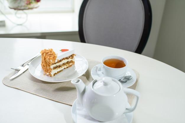 Вкусный морковный торт и чашка черного чая на столе в уютной кофейне