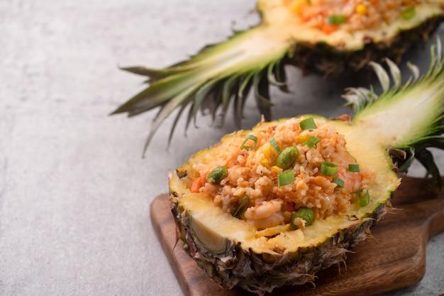 おいしい刻まれたパイナップルは、新鮮なパイナップルトマトソースのシーフードチャーハンを詰めたボウルコンテナボートとして機能しました。