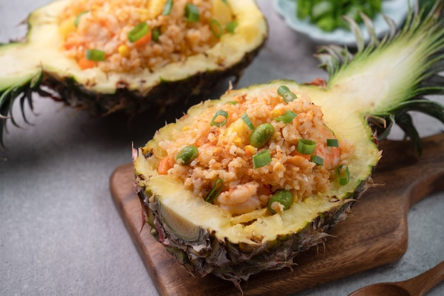 おいしい刻まれたパイナップルは、新鮮なパイナップル、トマトソース、シーフード、チャーハンを詰めたボウルコンテナとして機能しました