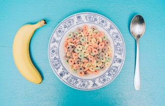 Delicious cereal loops on plate with banana and spoon against blue textured backdrop