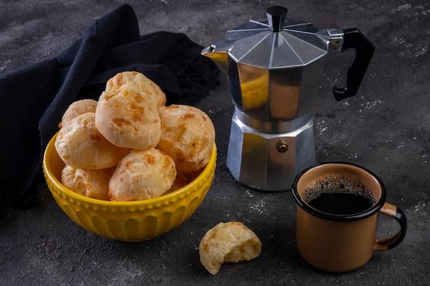 Вкусный сырный хлеб и кофейная кружка на темном фоне.