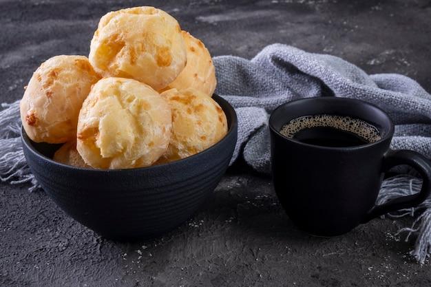 어두운 배경에 맛있는 치즈 빵과 커피잔.