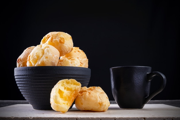 검은 배경의 흰색 대리석에 맛있는 치즈 빵과 커피 한 잔.