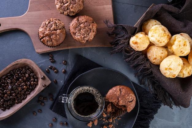 Вкусный сырный хлеб, шоколадные кексы и кофейная кружка.