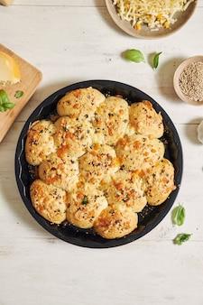 Delizioso pane per pizza con bolle di formaggio con ingredienti e formaggio su un tavolo bianco