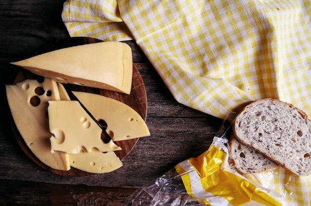 Вкусный сыр на деревянной доске и хлеб
