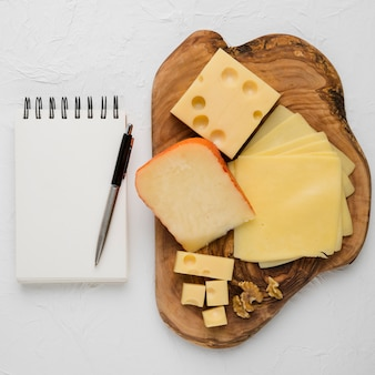 Delicious cheese platter and blank spiral dairy with pen against plain background