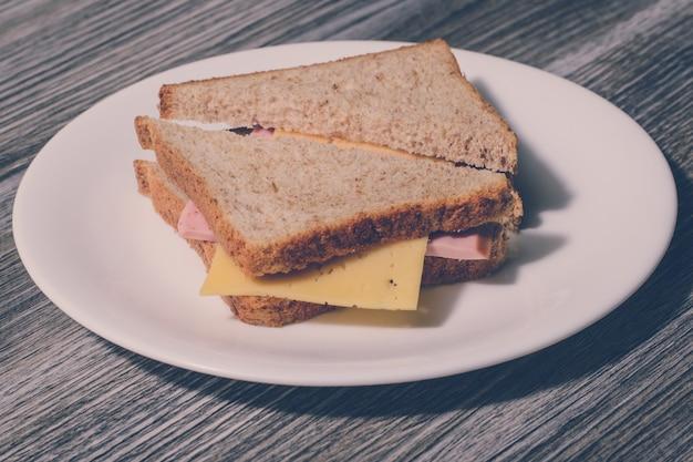 白い丸皿に美味しいチーズソーセージサンドイッチ。木製の背景、水平方向のビュー、ヴィンテージ効果