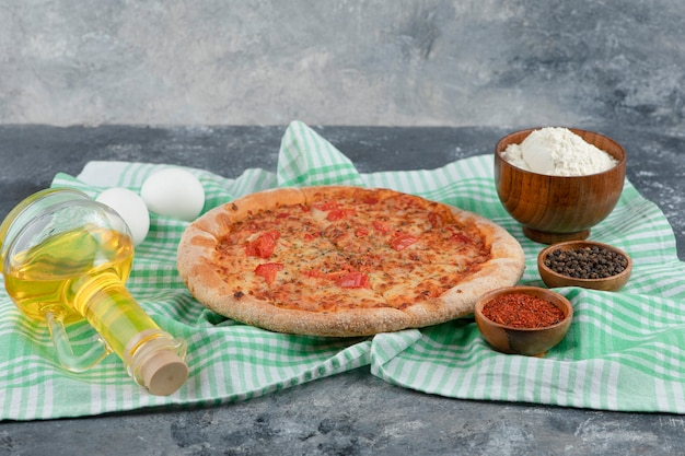 Delicious cheese and tomato pizza with flour and egg on stone background.