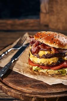 구운 쇠고기 패티에 샐러드 재료를 넣은 맛있는 치즈버거는 카피스페이스가 있는 소박한 나무 테이블에 있는 딱딱한 황금 빵 롤에 제공됩니다.