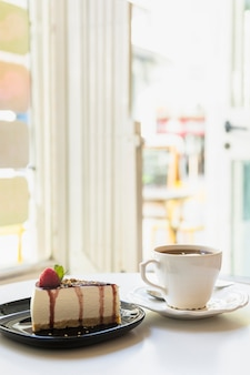 Delicious cheesecake slice and tea cup on white table near an open door
