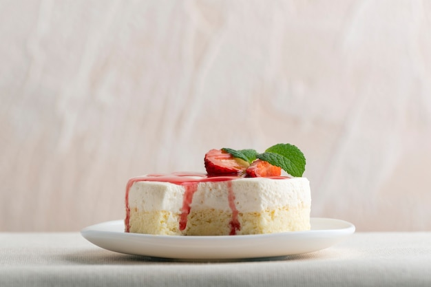 Delicious cheesecake with fresh strawberries and mint on white plate