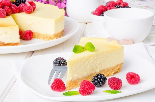 라즈베리와 블랙베리를 곁들인 맛있는 치즈 케이크. 전통적인 뉴욕 치즈 케이크. 미국 요리.