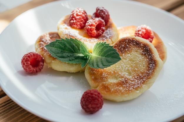 ラズベリーとミントの葉と木製のテーブルの上の白いプレートに粉砂糖を振りかけたおいしいチーズケーキまたはパンケーキ