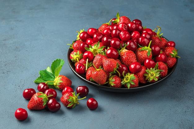 파란색 회색 배경에 검정 접시에 맛있는 체리와 딸기. 측면보기. 여름 과일과 열매.