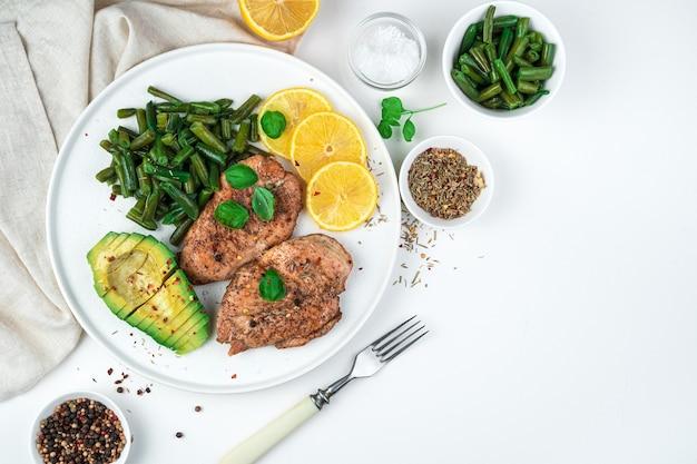 Вкусная куриная грудка с фасолью, авокадо, специями и лимоном на белом фоне. вид сверху, горизонтальный. концепция здорового питания.