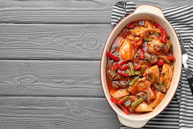 台所のテーブルの上のベーキング皿のおいしい鶏のカチャトーラ