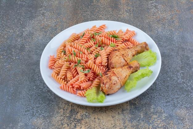 Cosce di pollo e maccheroni deliziosi sul piatto bianco. foto di alta qualità