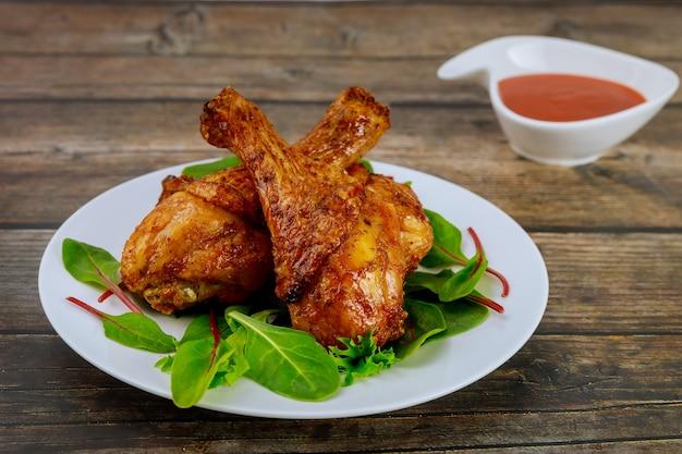 Вкусные куриные голени со шпинатом и соусом на деревянных фоне.
