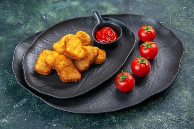 空きスペースのある暗い表面の黒い皿においしいチキンナゲットとケチャップトマト