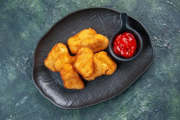 Deliziose crocchette di pollo e ketchup in piastre nere su superficie scura con spazio libero in primo piano