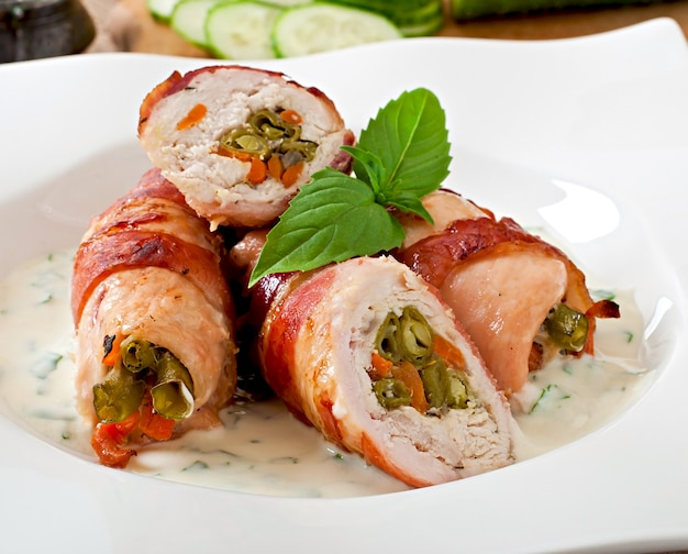 Delicious chicken rolls stuffed with green beans and carrots wrapped in strips of bacon