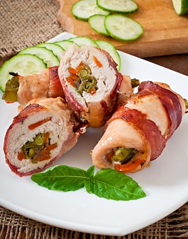 Delicious chicken rolls stuffed with green beans and carrots wrapped in strips of bacon Free Photo