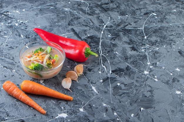 Вкусный куриный суп рядом с овощами, на мраморном фоне.
