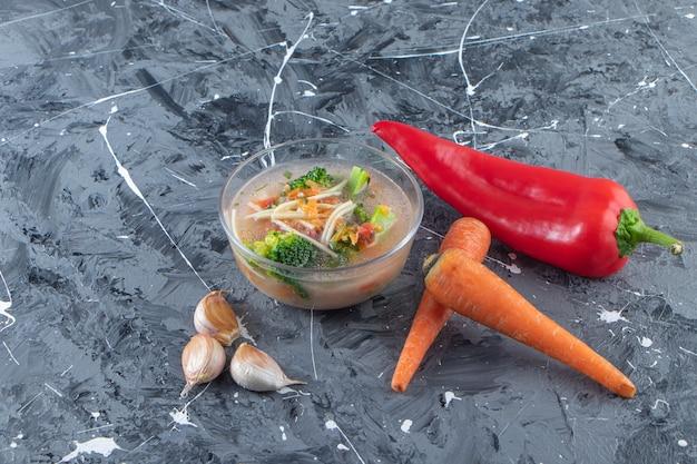 대리석 표면에 야채 옆에 맛있는 치킨 수프.